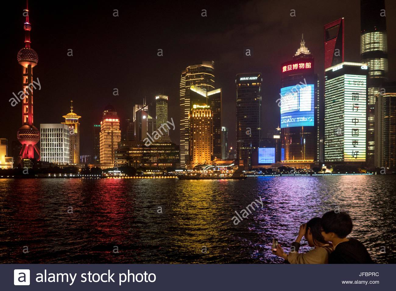 People taking a selfie on a cell phone on the Bund promenade. - Stock Image