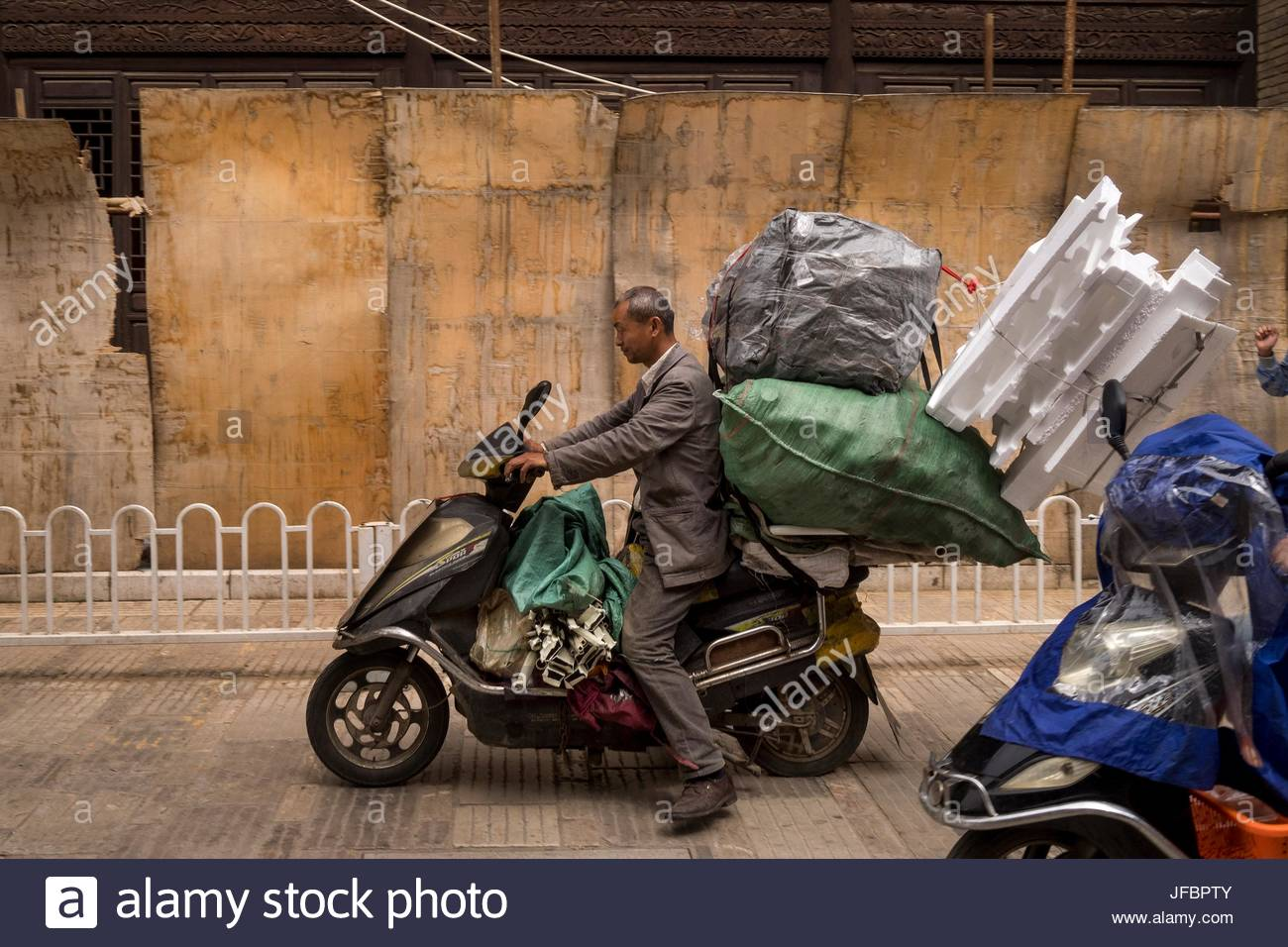 A man carries goods on his motor scooter past boarded up buildings on Guanghua Street. - Stock Image