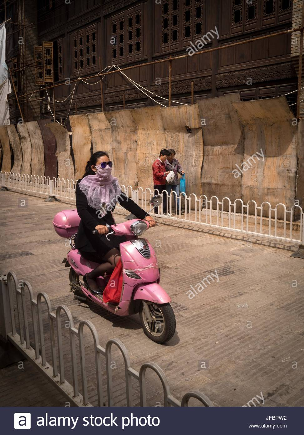 A woman wearing a face covering to protect against pollution, rides her motor scooter past boarded up buildings - Stock Image