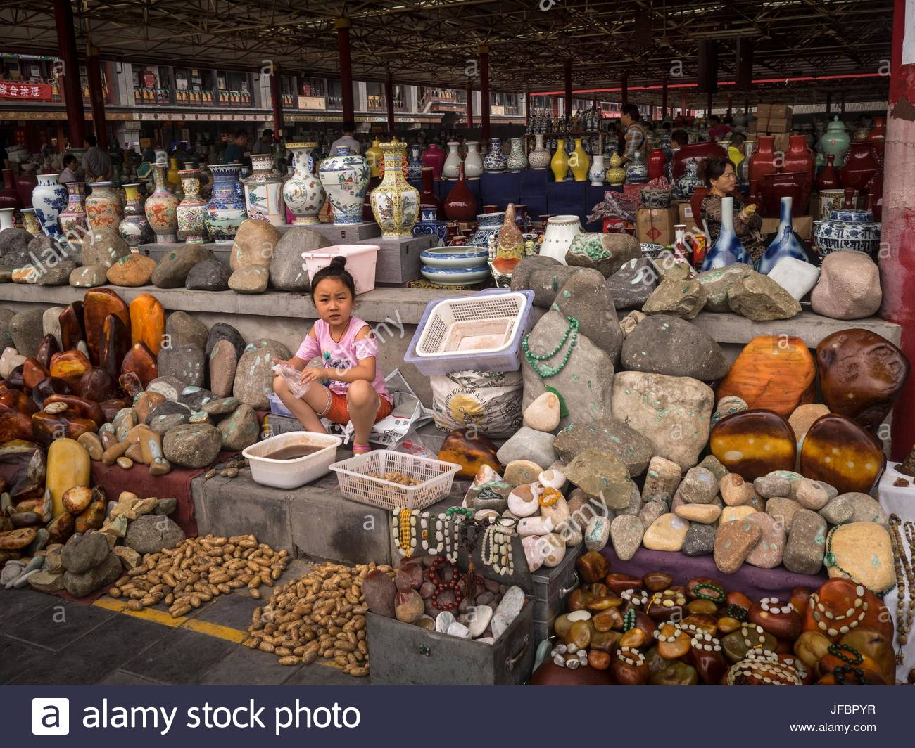 A young girl sits outside a ceramics and jewelry shop at the Panjiayuan Market. - Stock Image