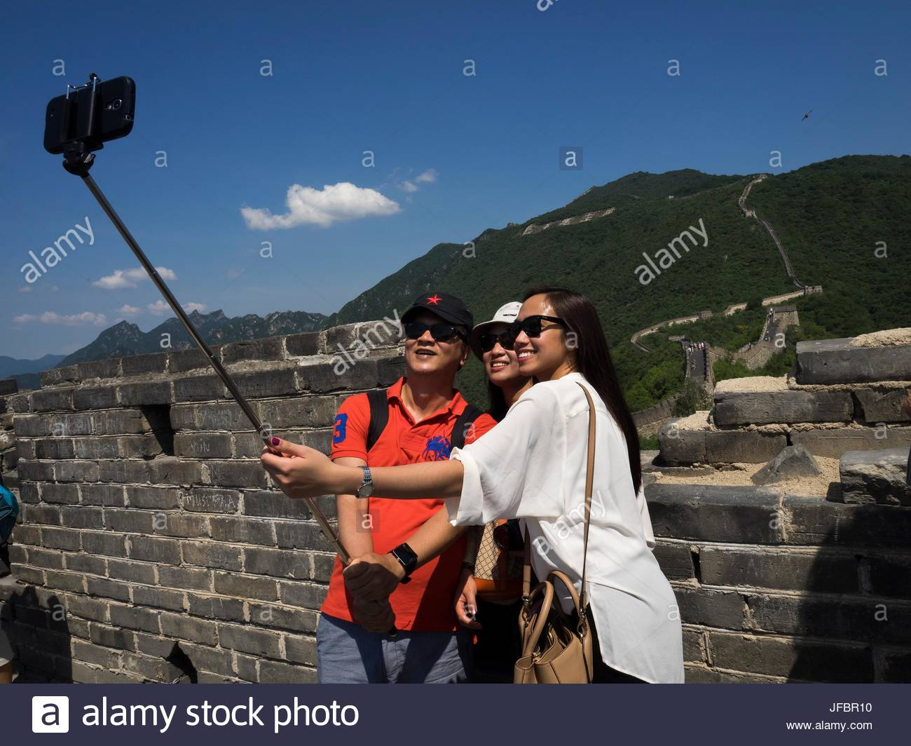 Teenagers shoot a selfie at the Great Wall of China, using a cell phone. - Stock Image