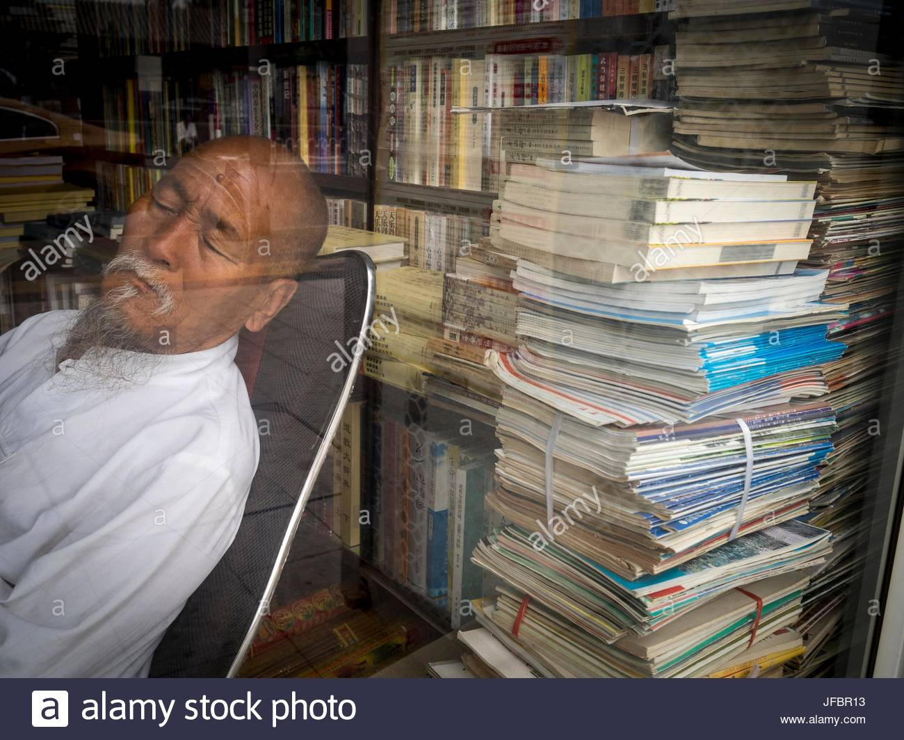A view, through a window, of a sleeping bookseller. - Stock Image