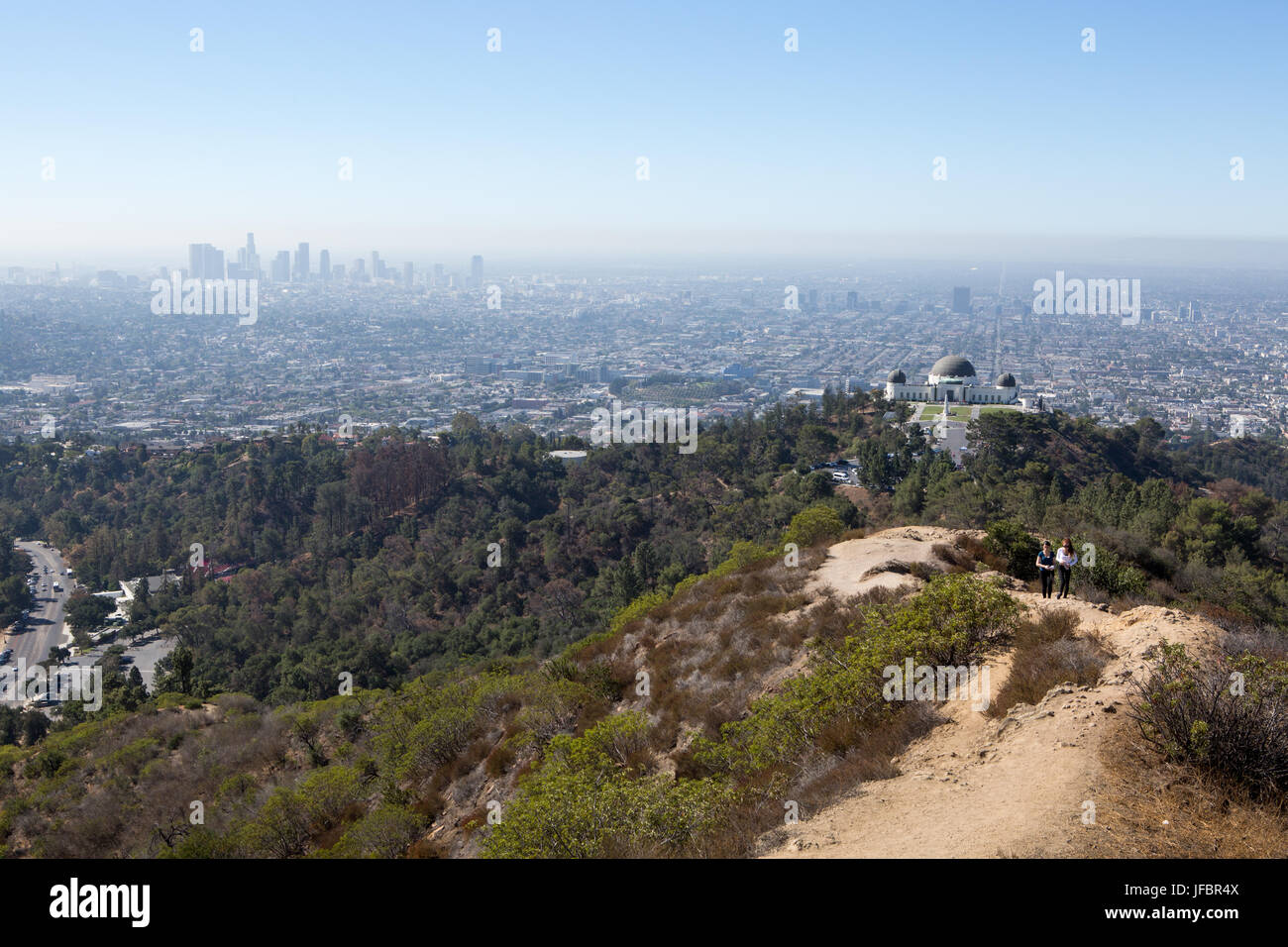 Hikers follow a path near Griffith Observatory. Air pollution hangs over Los Angeles. - Stock Image