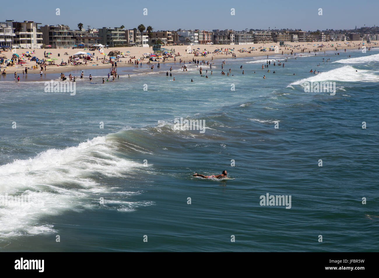 A surfer paddles out away from the crowds settled on Venice Beach. - Stock Image