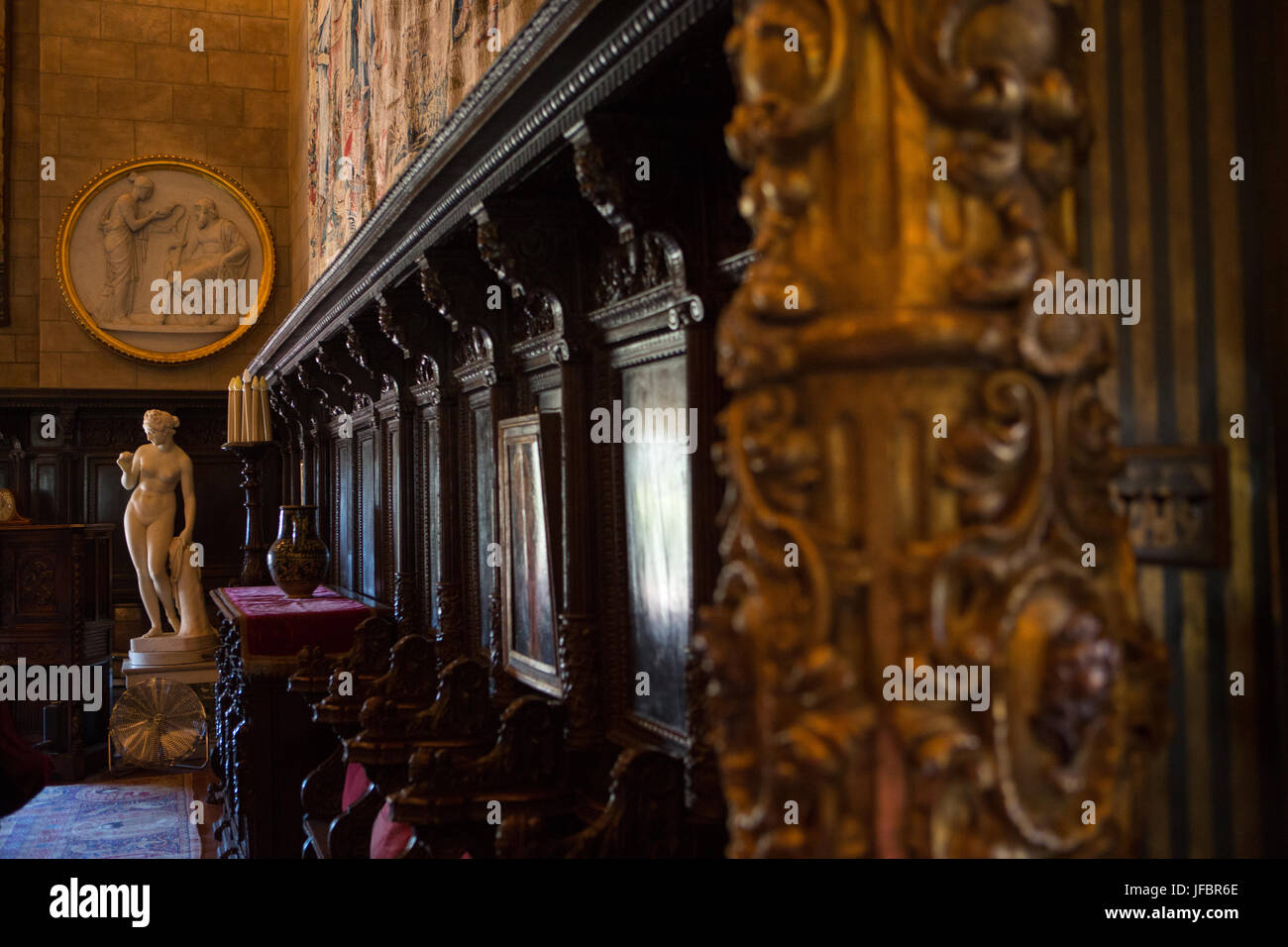 Hearst Castle interior walls are decorated with choir chair stalls, statues, and ornate decoration. - Stock Image