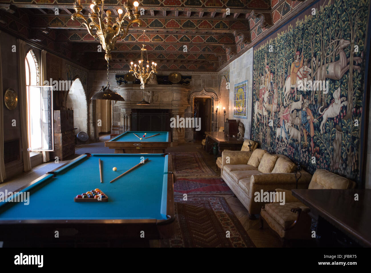 The Hearst Castle billiards room is decorated with furniture, tapestries, artwork and ornate light fixtures. - Stock Image