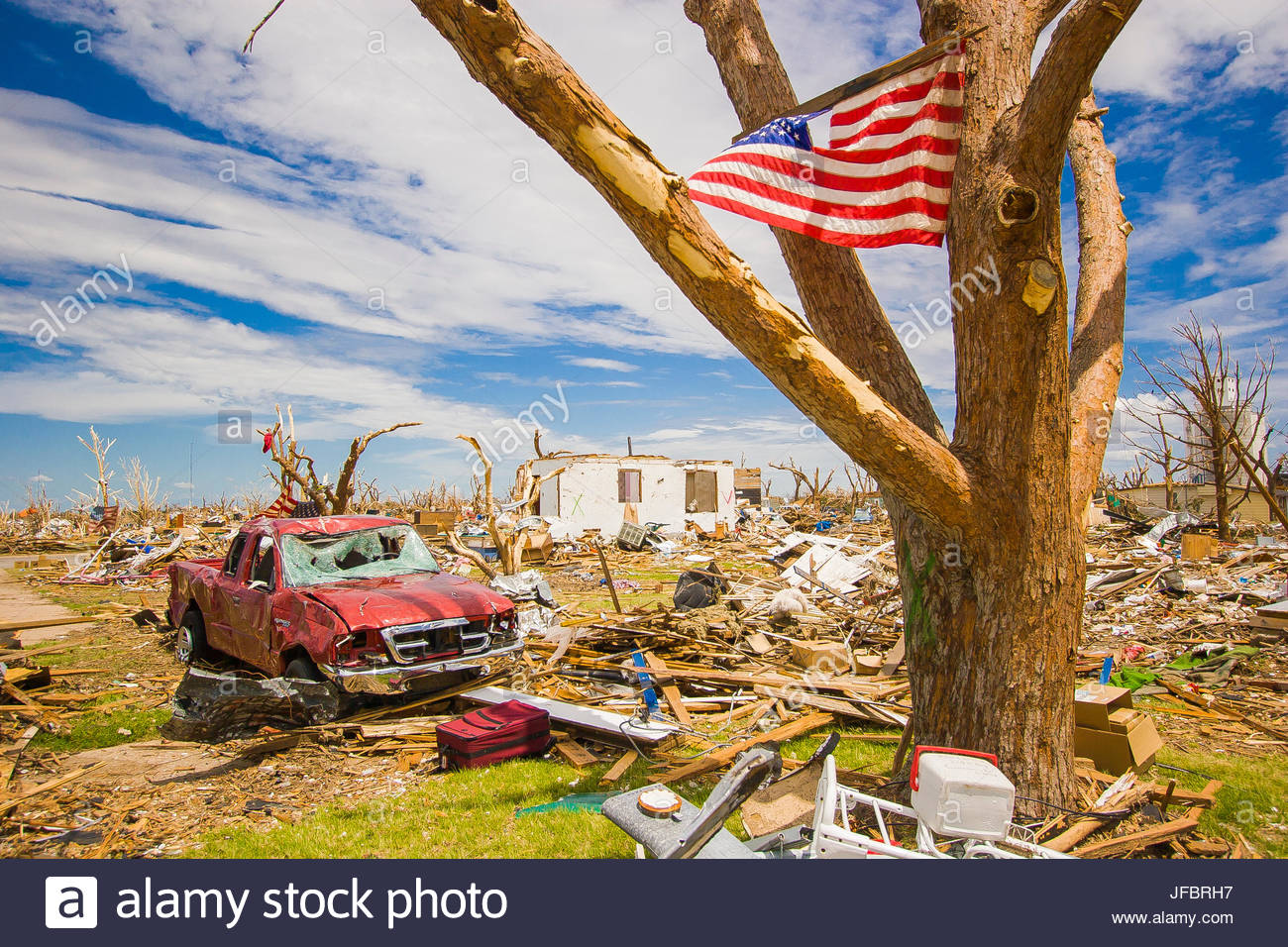 An American flag is attached to a tree to give strength to the town of Greensburg, Kansas after an EF-5 Tornado - Stock Image