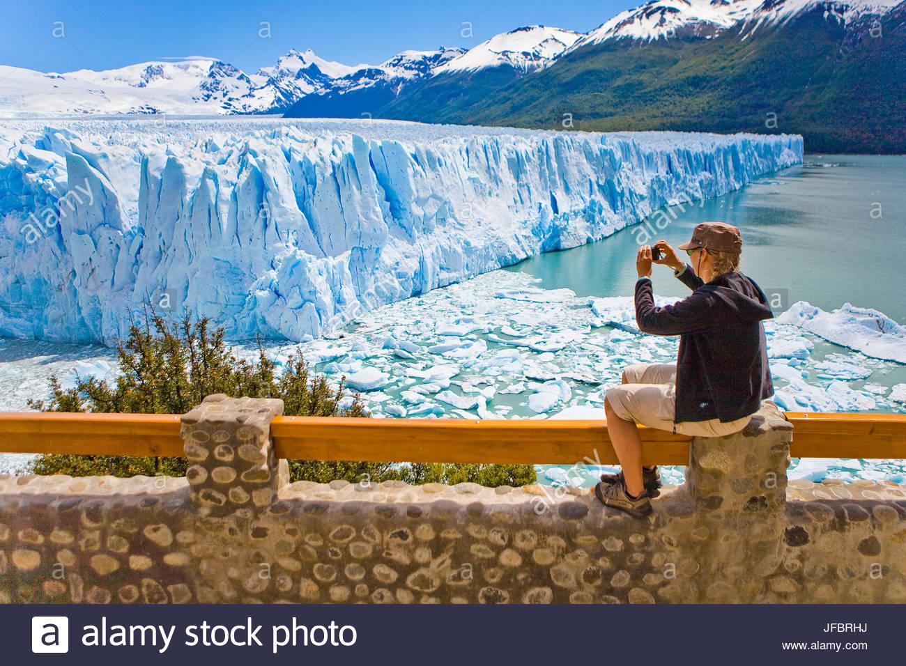 A woman takes a photo of the Perito Moreno glacier in Argentina. - Stock Image