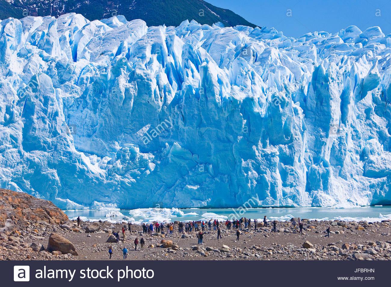 Tourists view the massive front wall of the Perito Moreno glacier in Argentina. - Stock Image