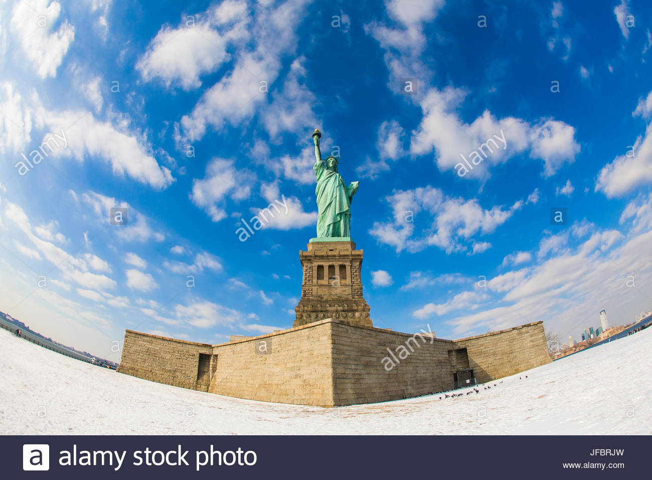 Fisheye lens view of the Statue of Liberty in New York during the winter with snow on the ground and blue skies. - Stock Image