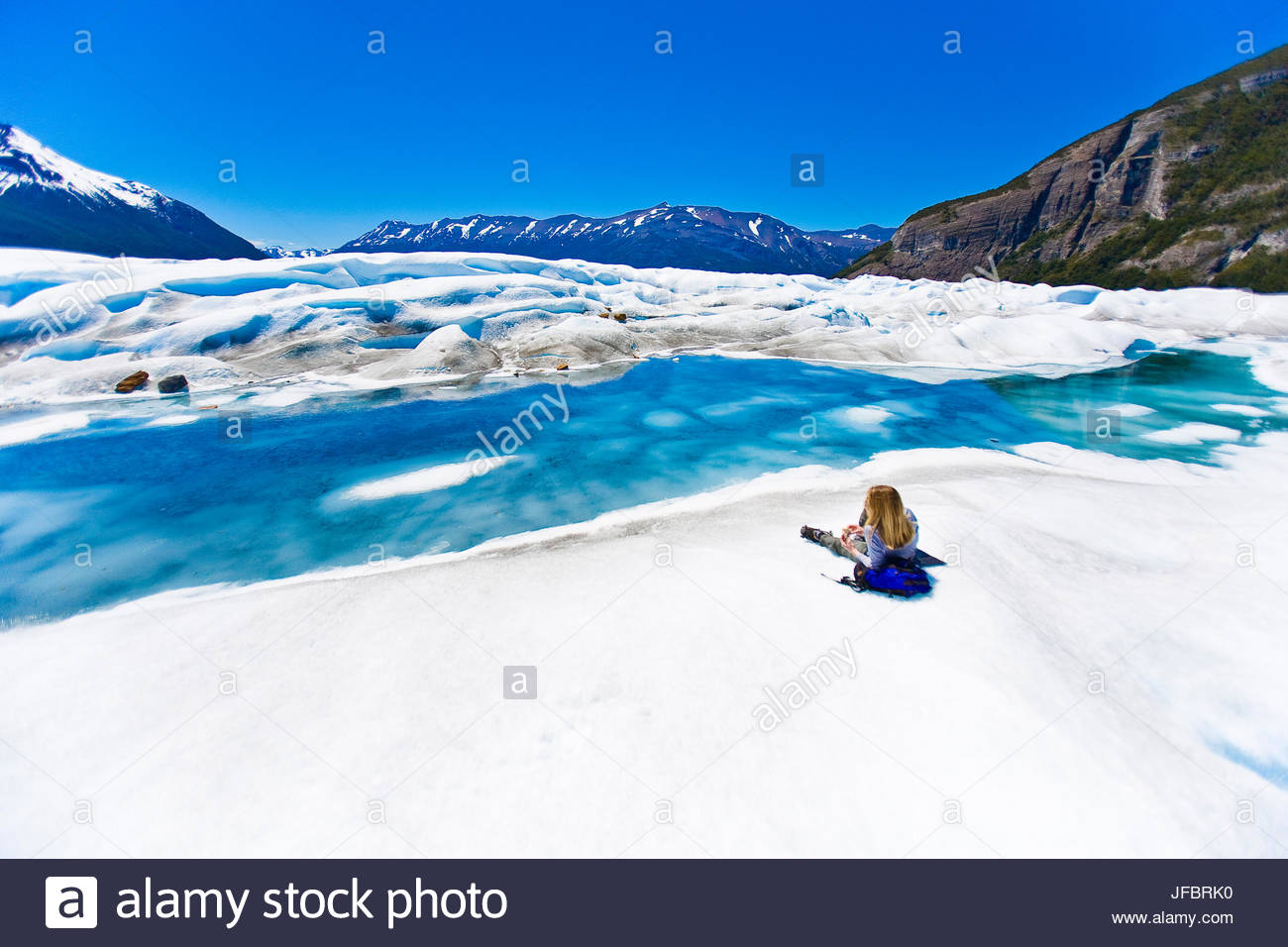 A hiker relaxing and taking a rest after exploring on the surface of the Perito Moreno glacier in Argentina. - Stock Image