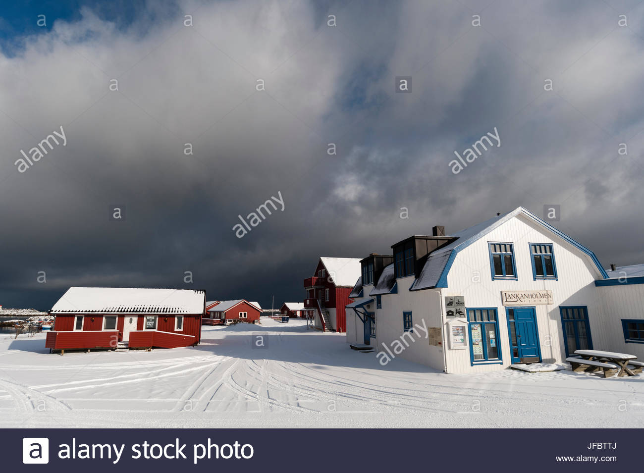 Snow-covered houses and roads under a cloudy sky. - Stock Image