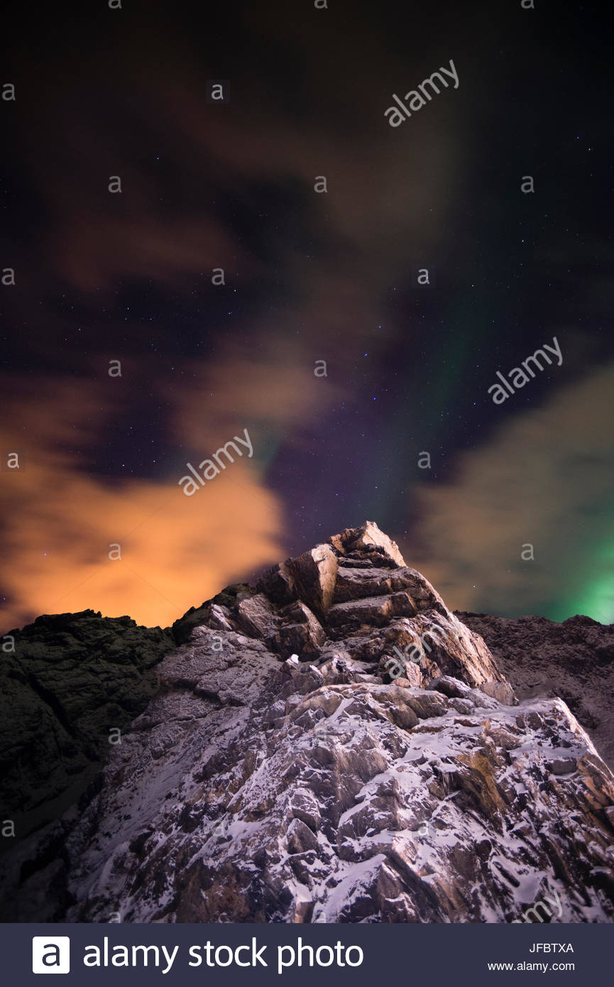 An aurora borealis behind a mountain peak in Andenes. - Stock Image