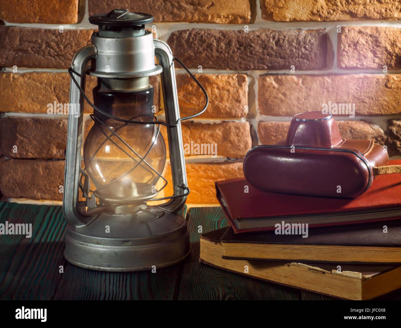 Still life kerosene lamp shines on  wooden desktop  stone brick background book camera - Stock Image