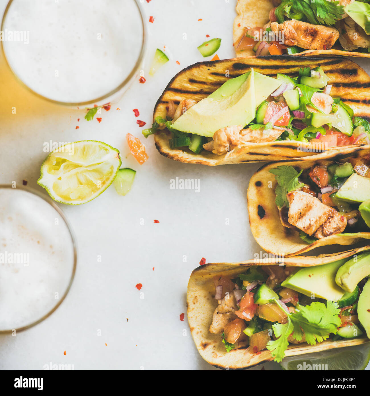 Healthy corn tortillas with chicken, vegetables, limes, square crop - Stock Image
