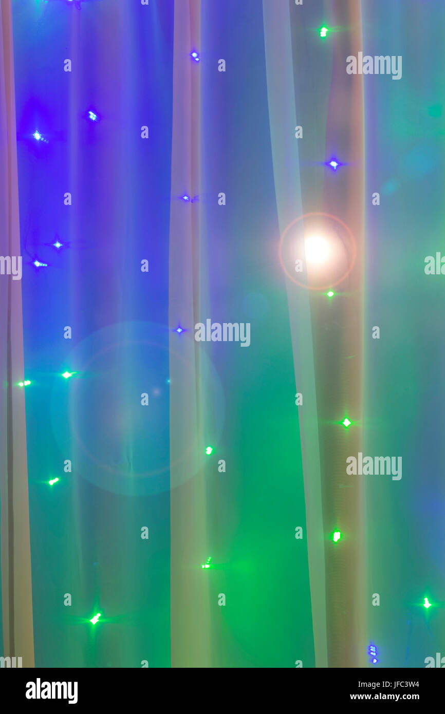 Christmas lights in the window on the background of transparent tulle. Stock Photo