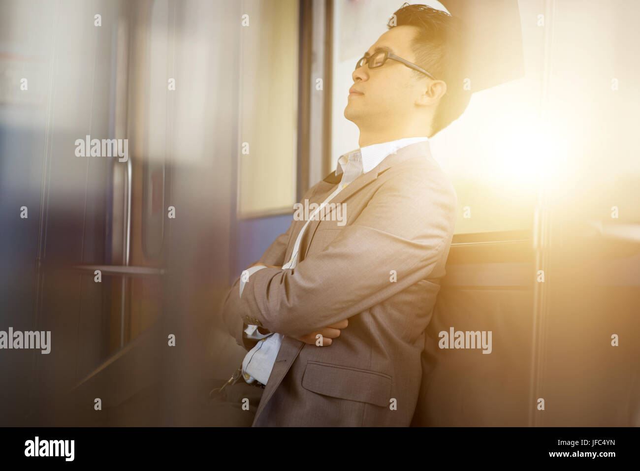 Asian businessman taking a nap inside train while travelling to work. - Stock Image