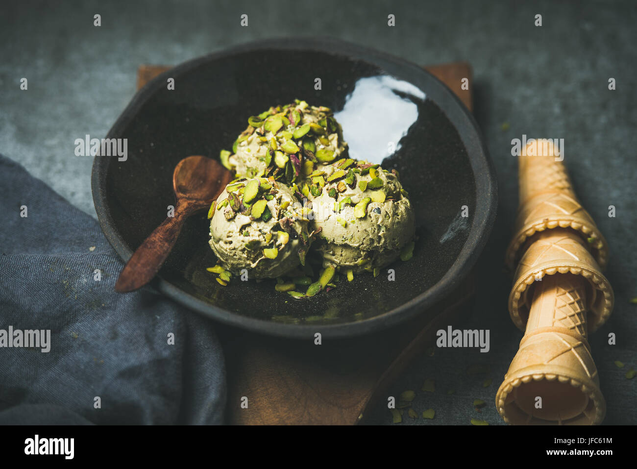 Homemade pistachio ice cream scoops with crashed nuts in plate - Stock Image