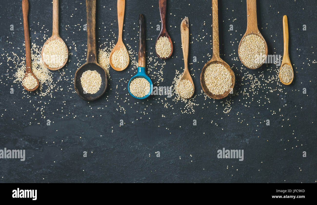 Quinoa seeds in spoons over black stone background, copy space Stock Photo