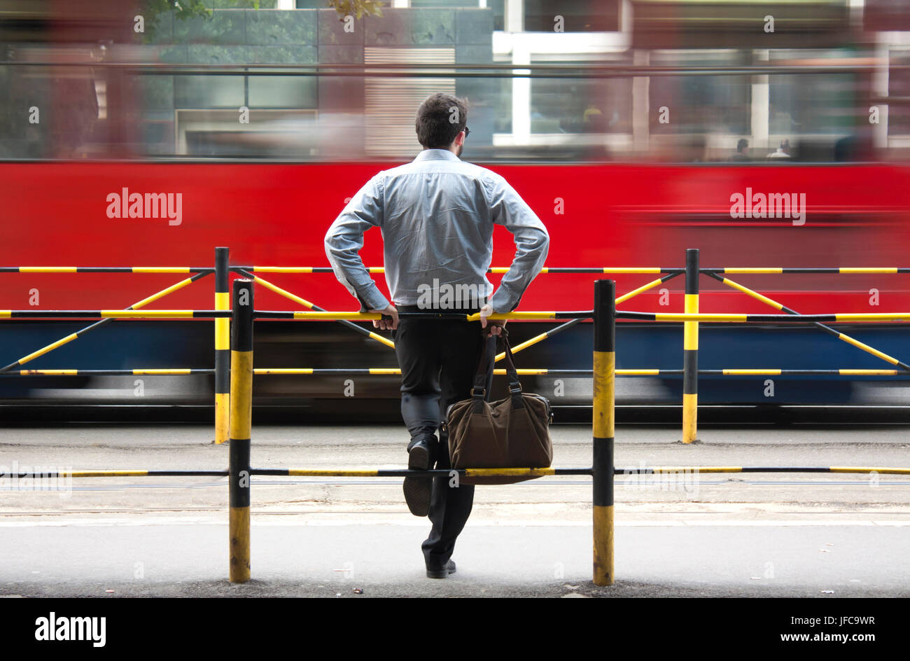 One young man waiting for public transport at bus stop Stock Photo