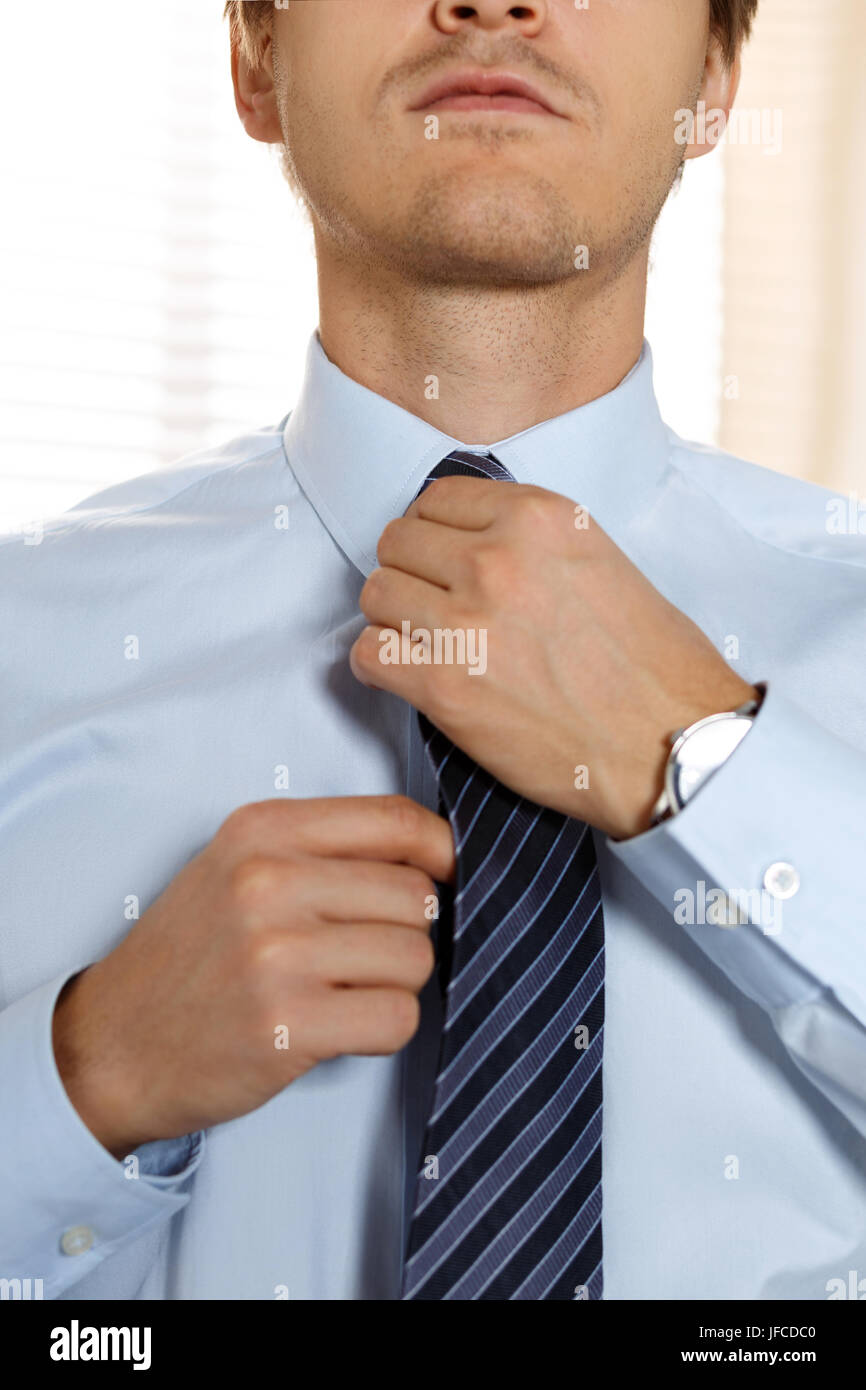 Handsome businessman preparing to official event straighten tie handsome businessman preparing to official event straighten tie new job interview self motivation for confidence trying fashionable necktie knot ccuart Images