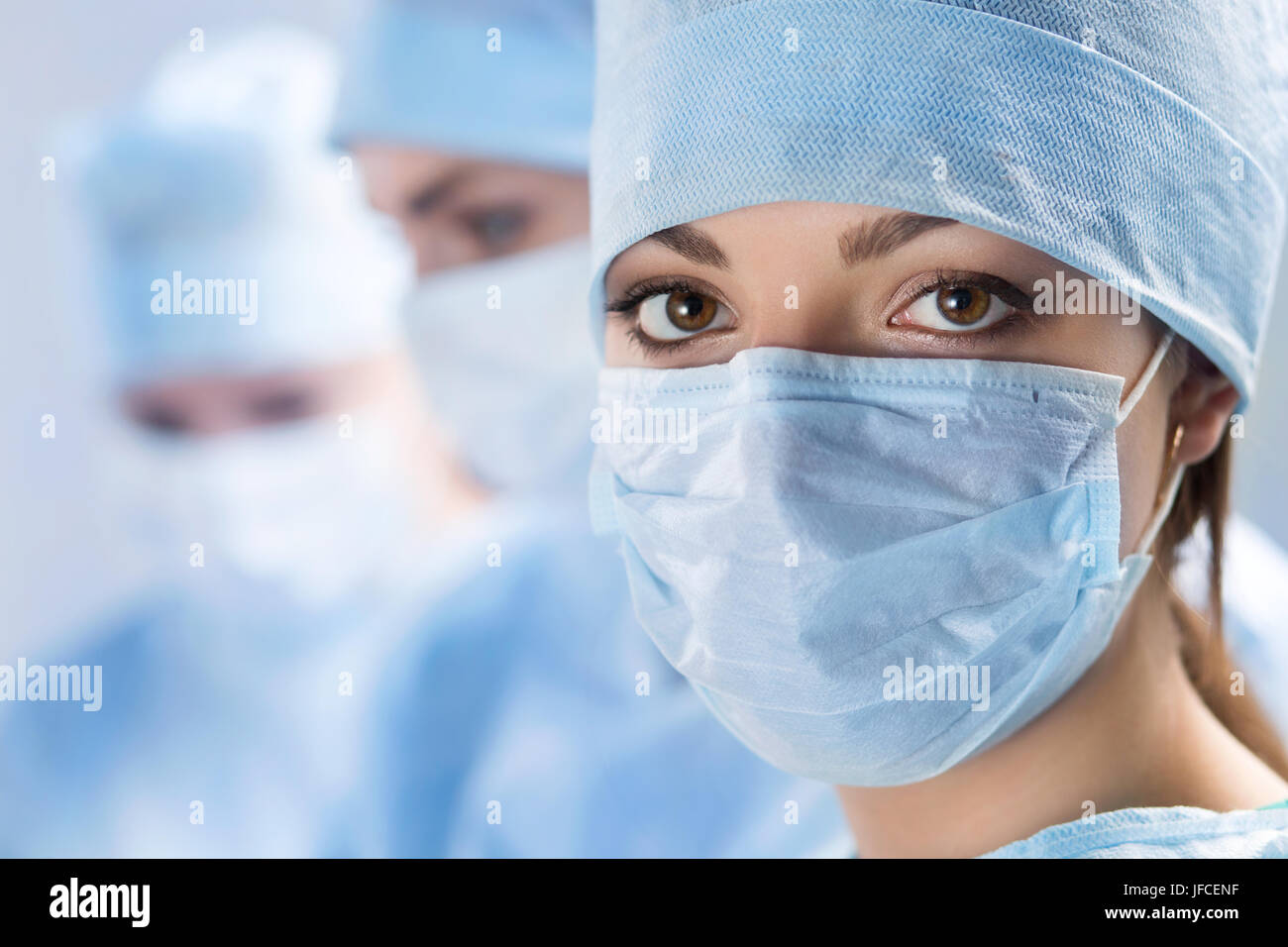 Close up portrait of young female surgeon doctor surrounded by her team. Group of surgeon in operation theatre. - Stock Image