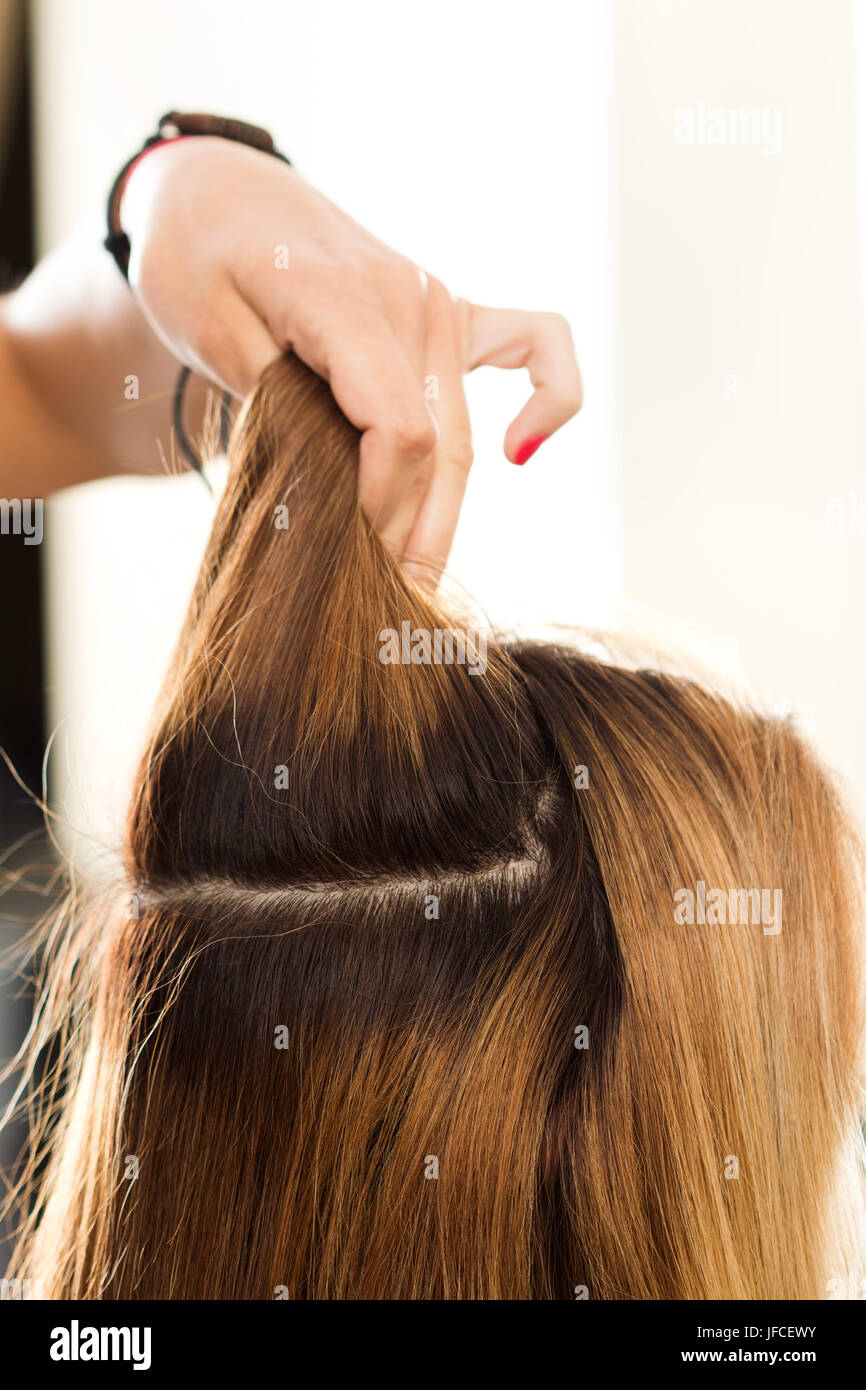 Close up view of hairdresser hand holding strand of hair preparing to cutting and dyeing hair. Haircare, making - Stock Image