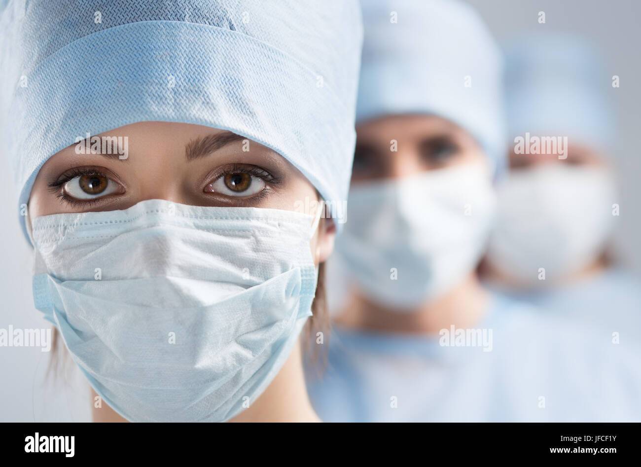 Close-up portrait of young female surgeon doctor surrounded by her team. Group of surgeon in operation theatre. - Stock Image