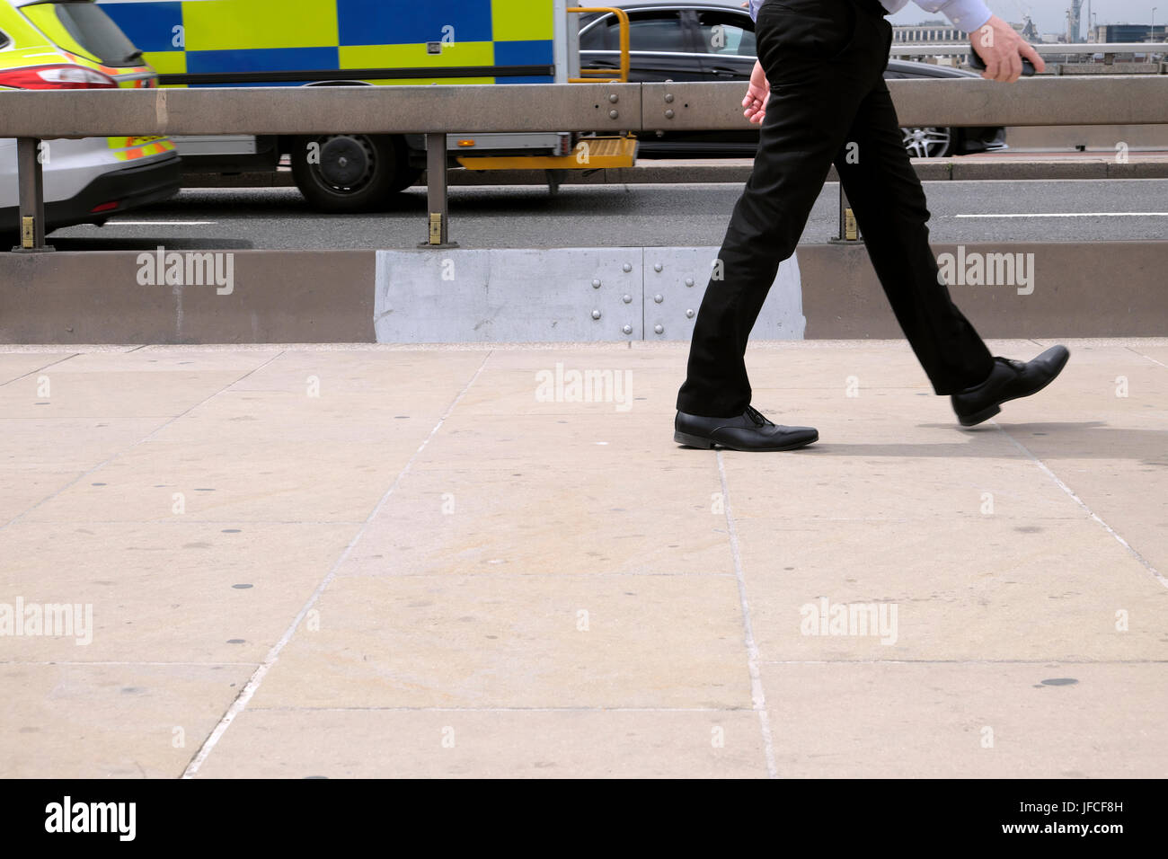 Commuter office worker walking along pavement next to anti-terrorist  concrete barriers over London Bridge and ambulance - Stock Image