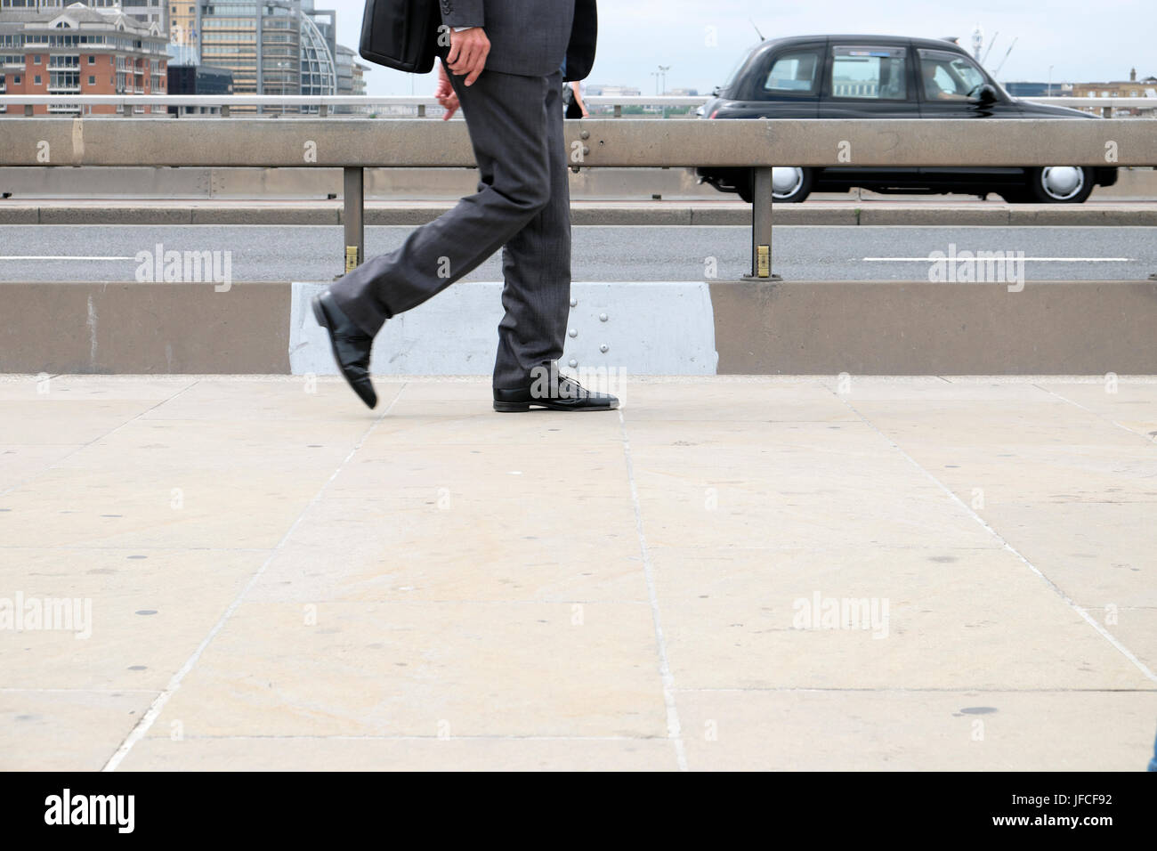 Businessman walking to work along pavement next to anti-terrorist concrete barrier over London Bridge after 2017 - Stock Image