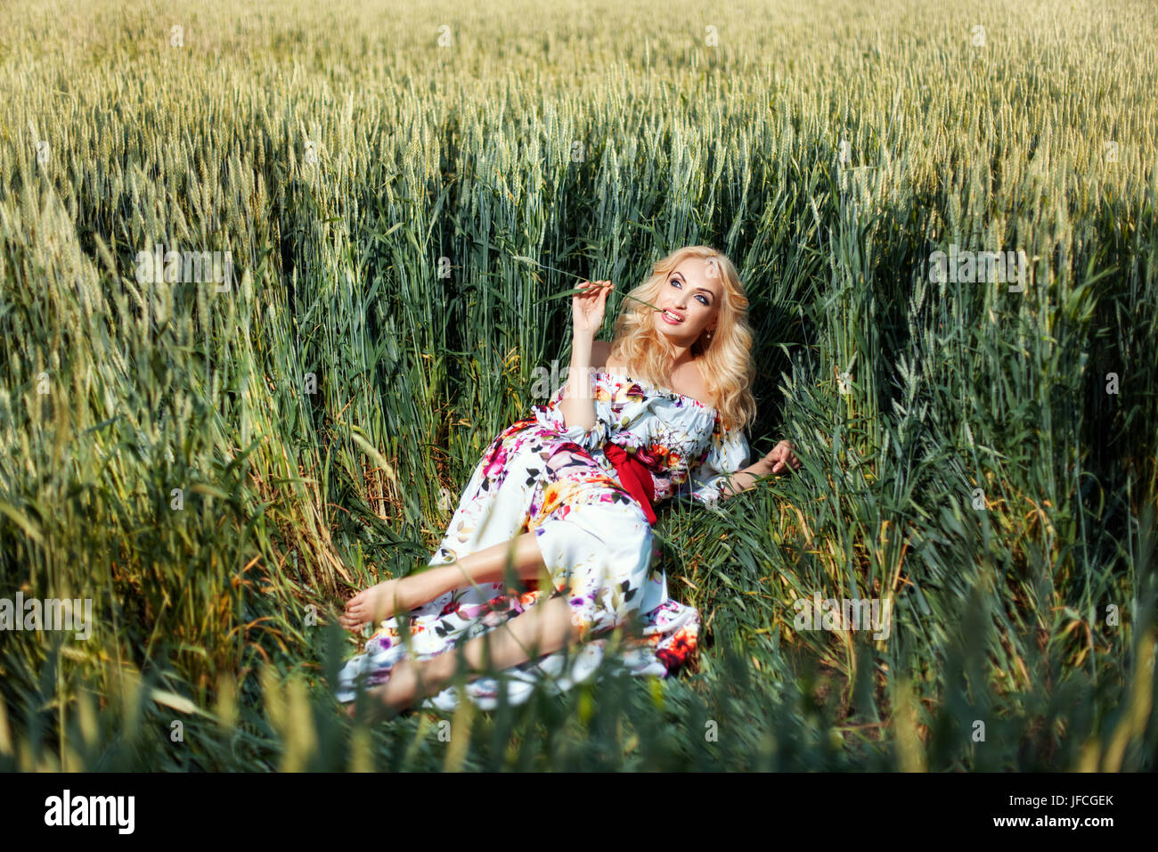 Girl lies on a rumpled grass on the field. She keeps flirting ears of corn mouth. - Stock Image
