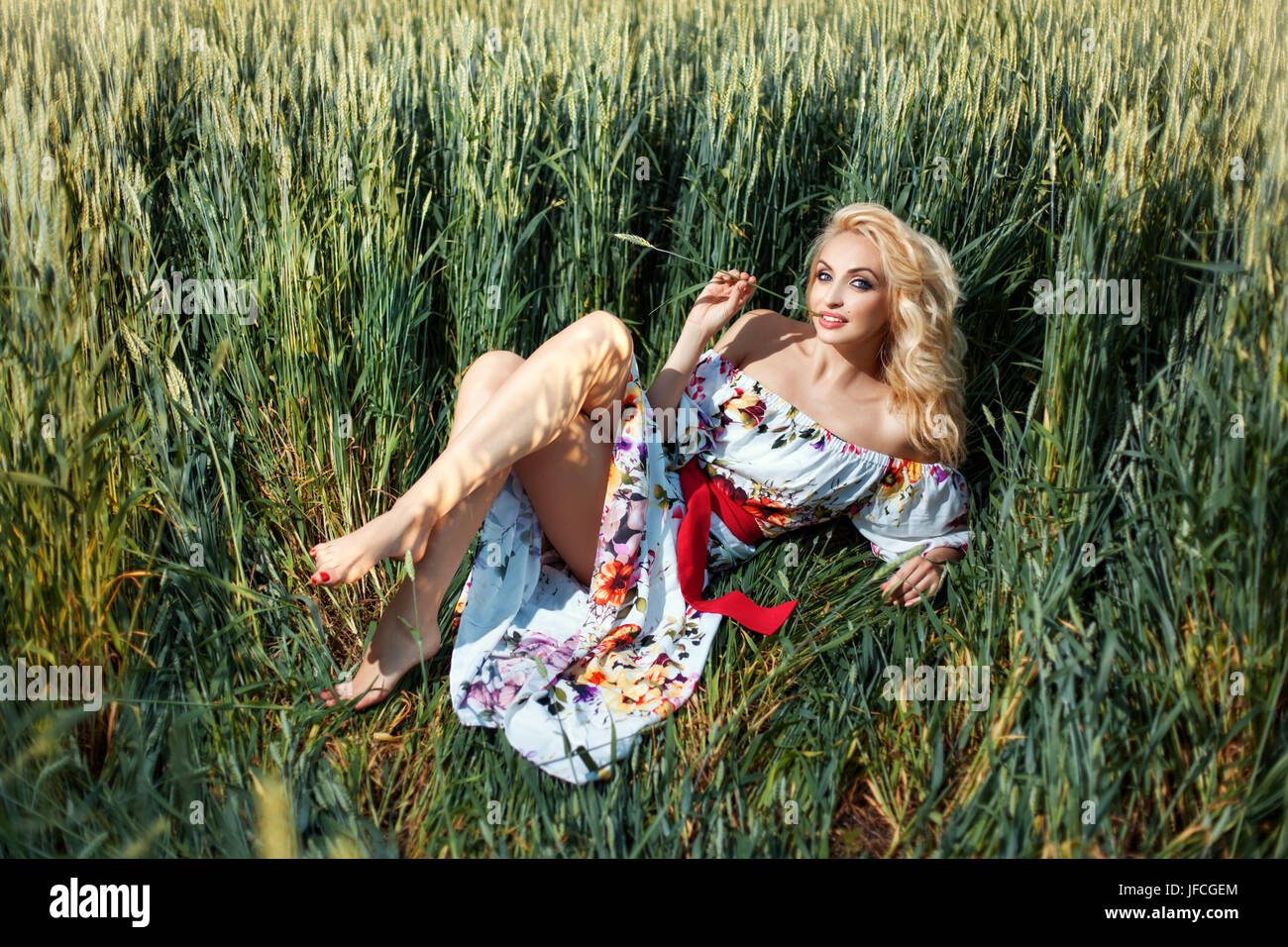 Beautiful girl on the field among the ears of corn. She flirts. Her mouth spikelet. - Stock Image