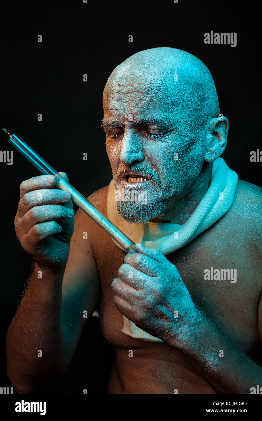 The bald man looks at the thermometer. He has a mustache and beard. His head was frozen and covered with frost. - Stock Image