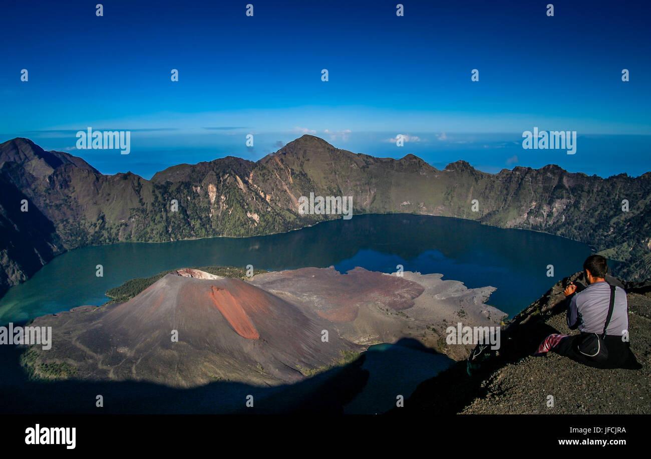 Tourist sitting on the rim of the crater of Gunung Rinjani volcano in Lombok island,  Indonesia Stock Photo