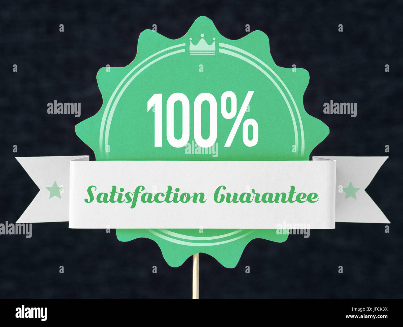 100% satisfaction guarantee badge cut from cardboard and paper on a wooden stick. Green banner, seal and ribbon - Stock Image