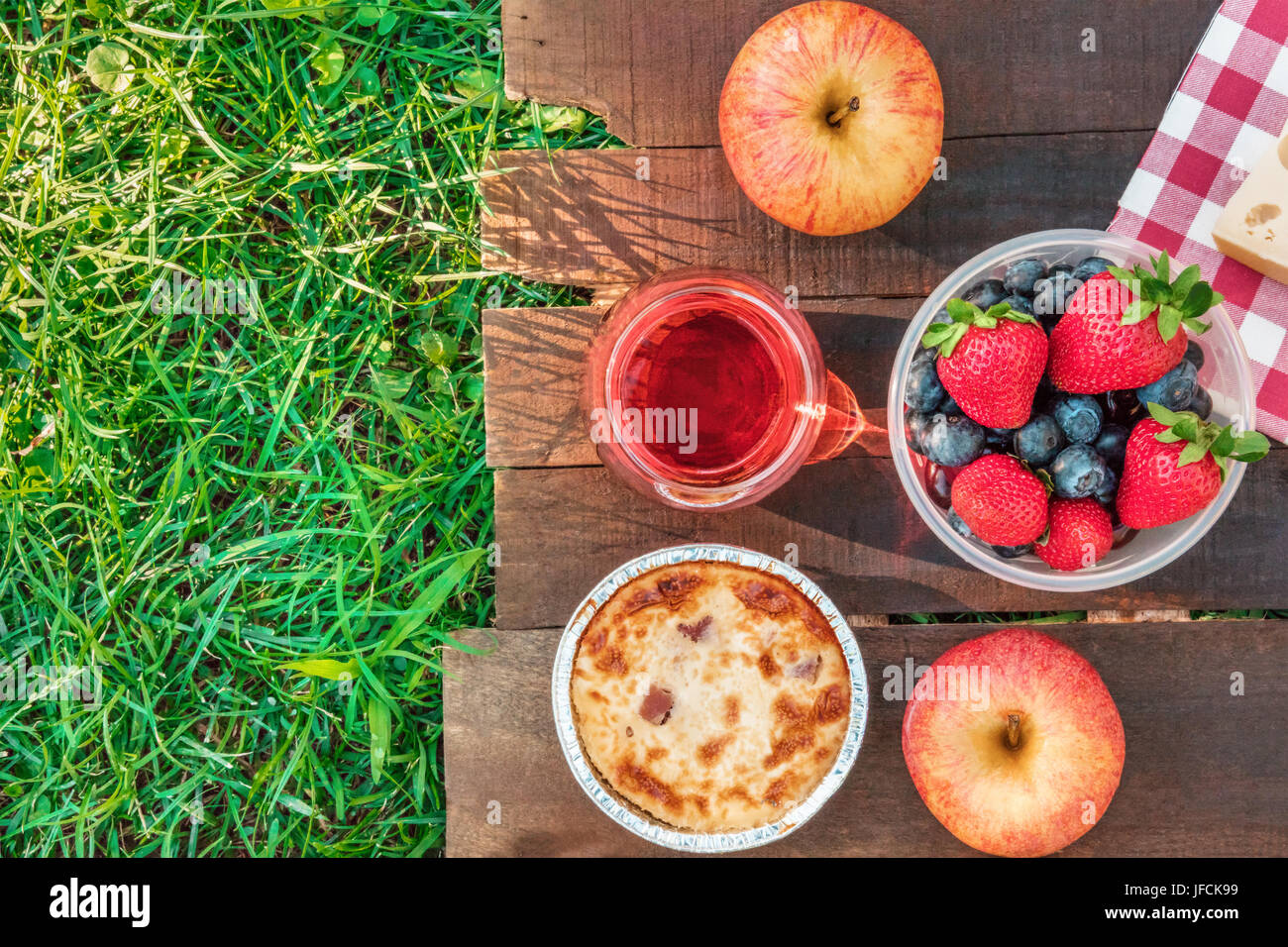 An overhead photo of a picnic with an apple, a glass of rose wine, fresh fruit in a plastic container, and a quiche, - Stock Image