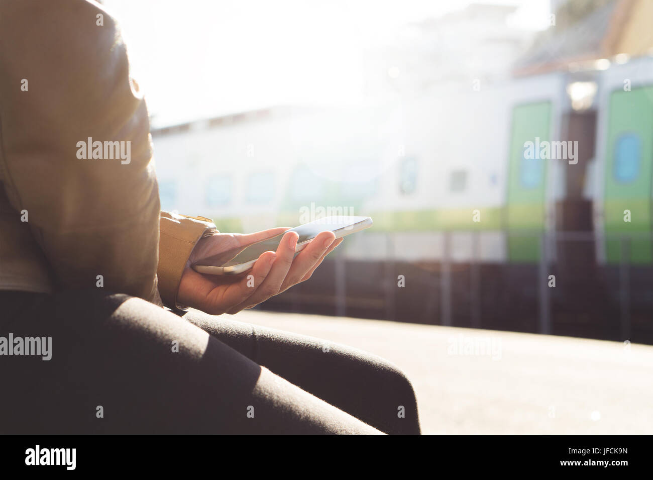 Woman buying ticket or checking schedule with mobile phone in the train platform. Smartphone and trainModern public - Stock Image