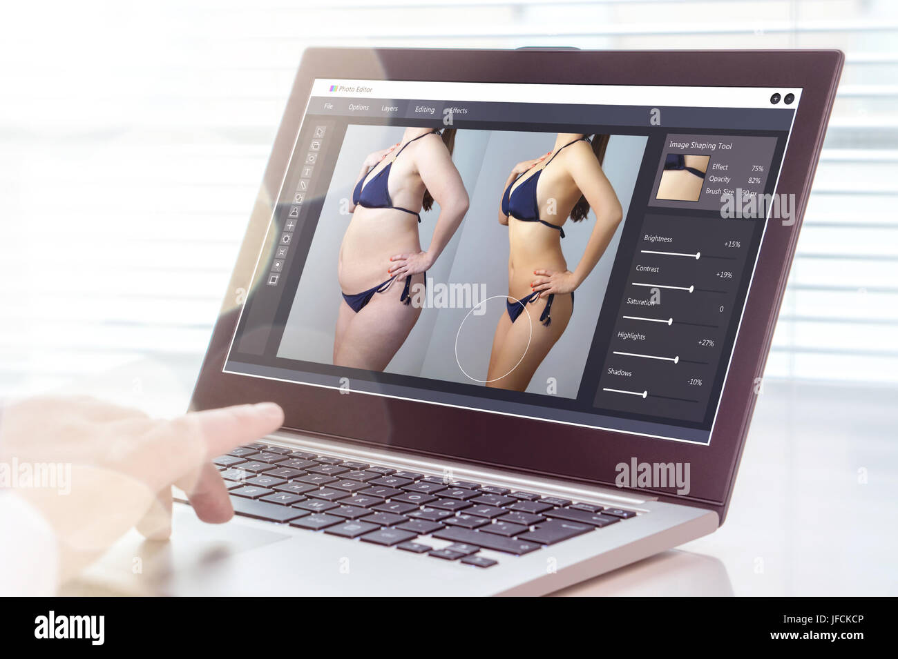 Professional man using laptop to transform chubby woman slim. Heavy photo editing with computer software. Standard - Stock Image