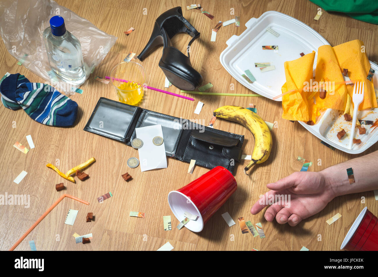 Hangover after partying. Man lying on the floor, hand visible. Trash, food leftovers, clothes, high heels and bottles - Stock Image