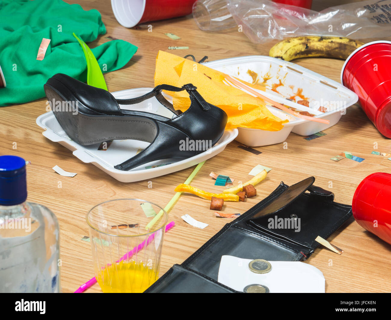 High heels, food leftovers and trash everywhere after awesome party. Next morning regret and remorse. Messy home - Stock Image
