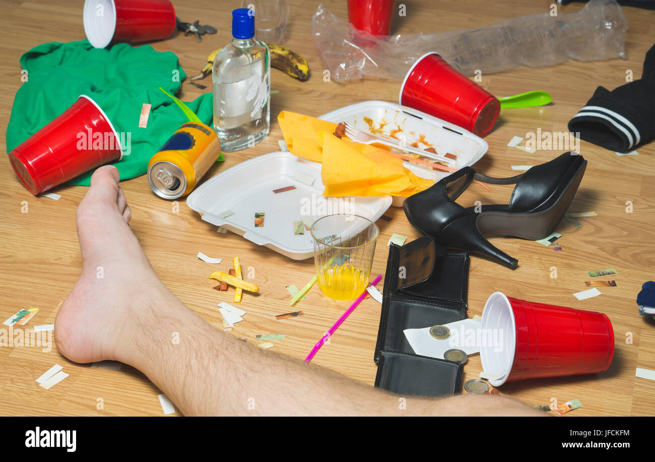 Hung over man passed out on the floor next day to a party, foot visible. Trash, food leftovers, clothes, high heels - Stock Image