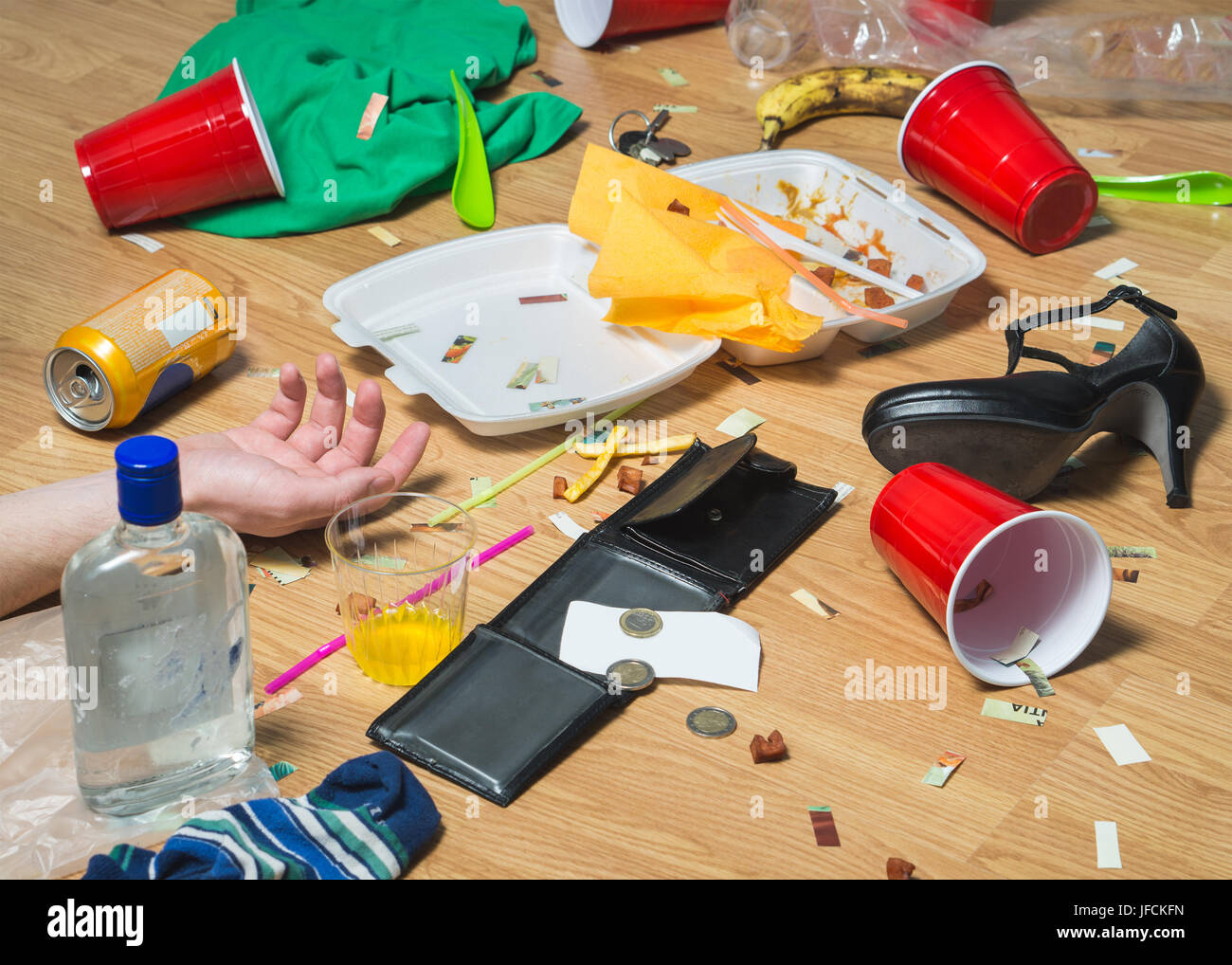 Man passed out on the floor after wild partying, hand visible. Terrible hangover and mess in the apartment. Trash, Stock Photo