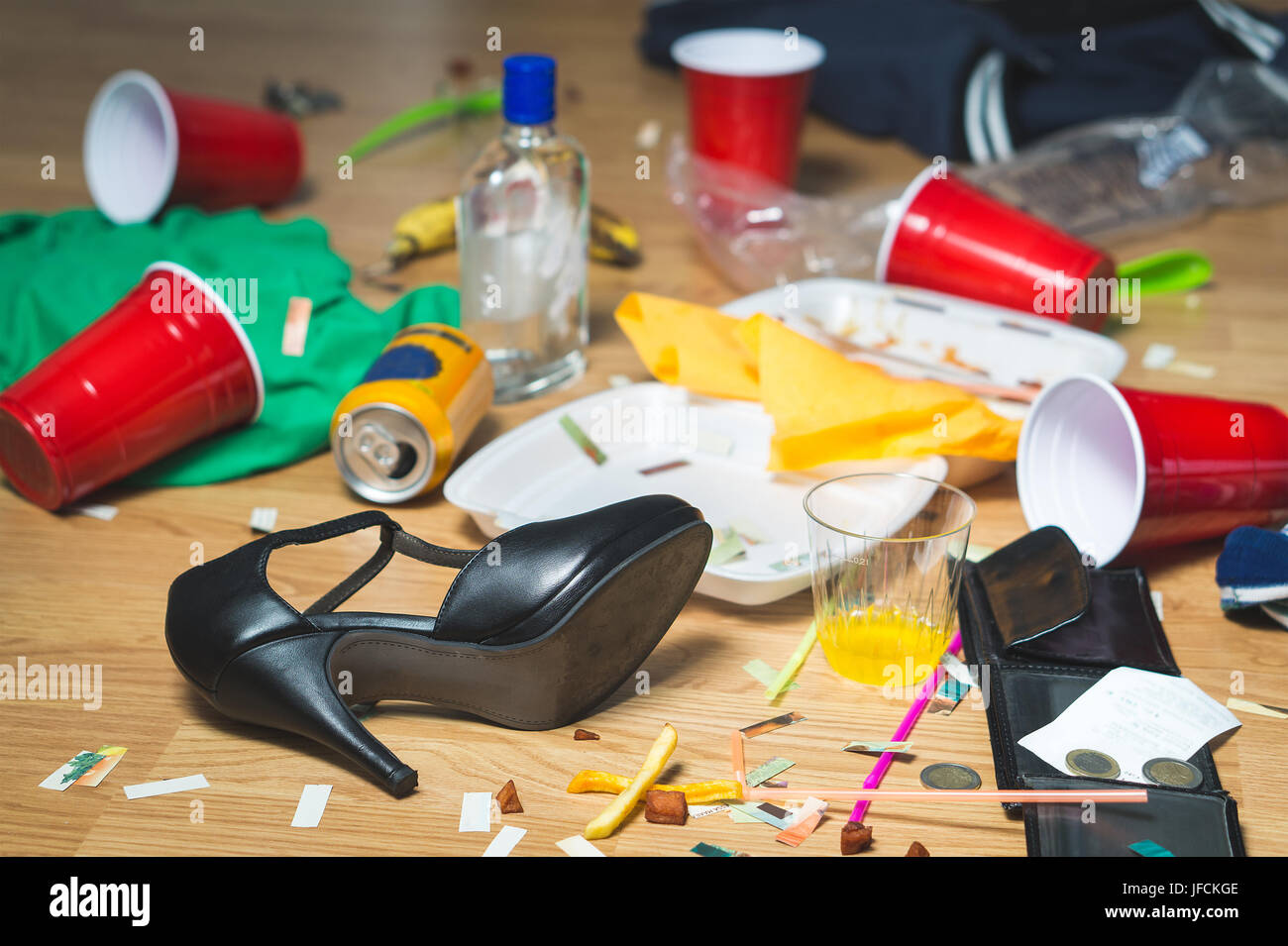 Terrible mess after party. Trash, bottles, food, cups and clothes on the floor. Messy apartment after guests leaving - Stock Image