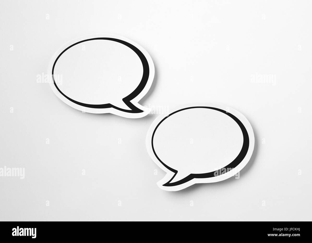 2 blank speech bubbles on white paper background. Chat bubble cut from cardboard. Simple and effective design. Discussion, - Stock Image
