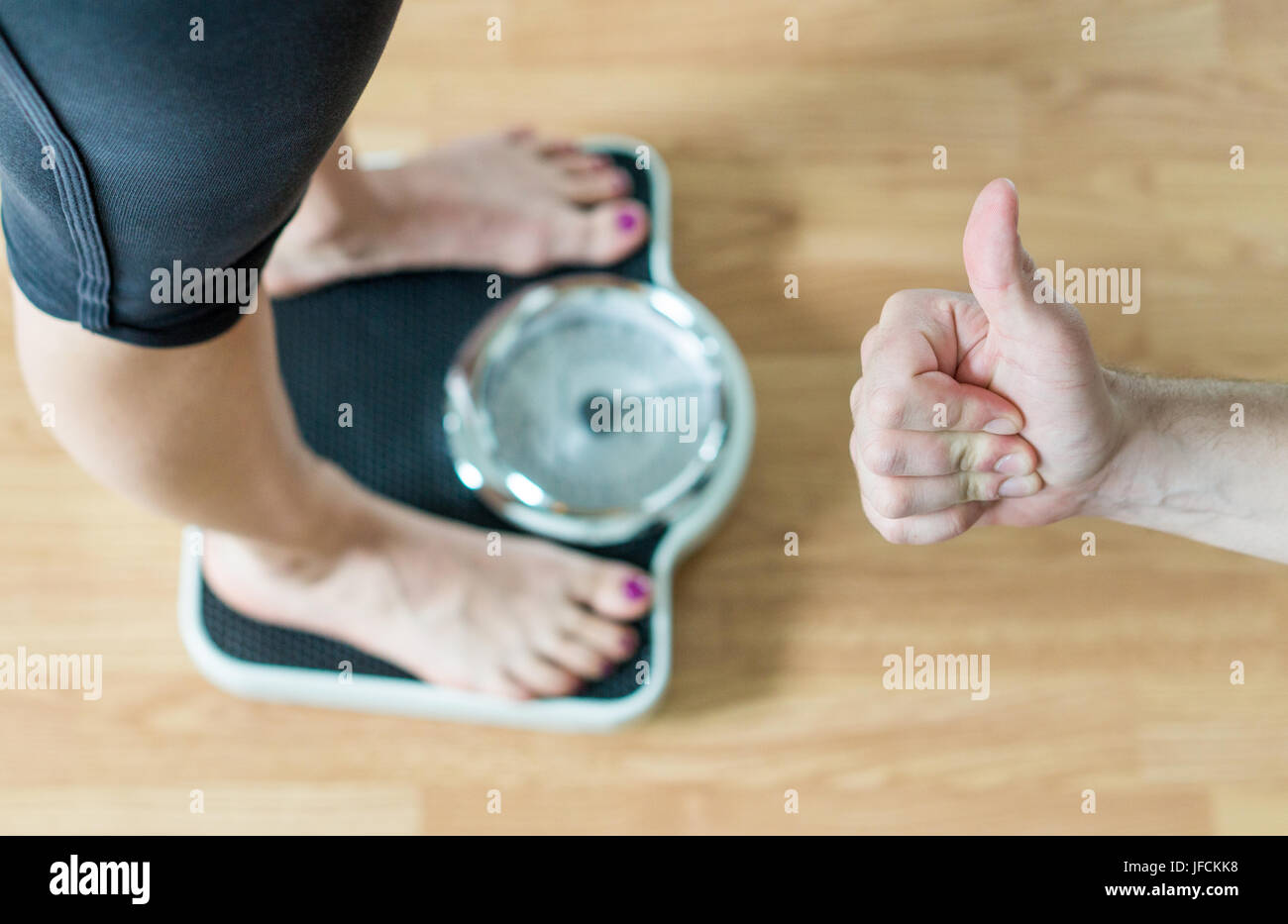 Personal trainer or coach giving thumbs up to a person standing on scale. Success and great achievement in weight - Stock Image