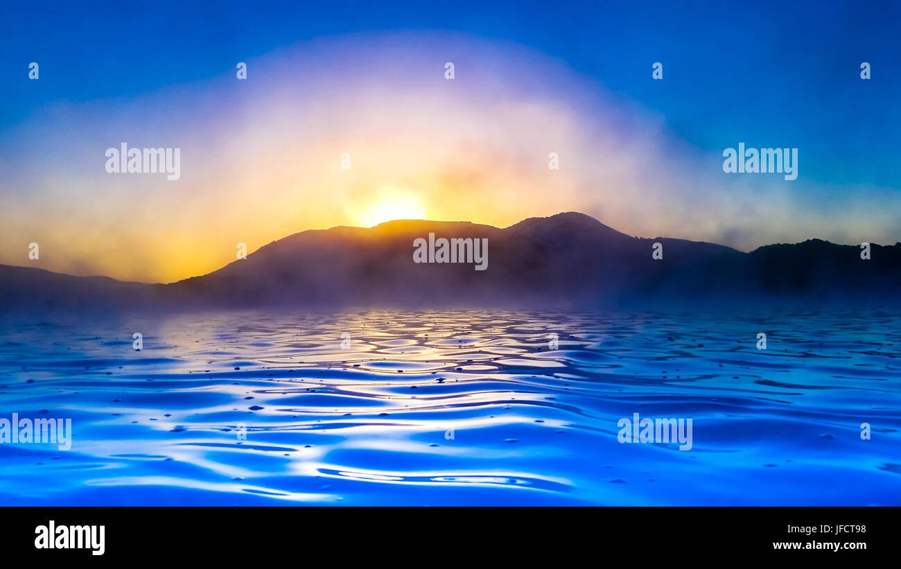 Color enhanced scene of a blue inky sea with a dark mountainous skyline silhouetted against an orange setting sun. - Stock Image