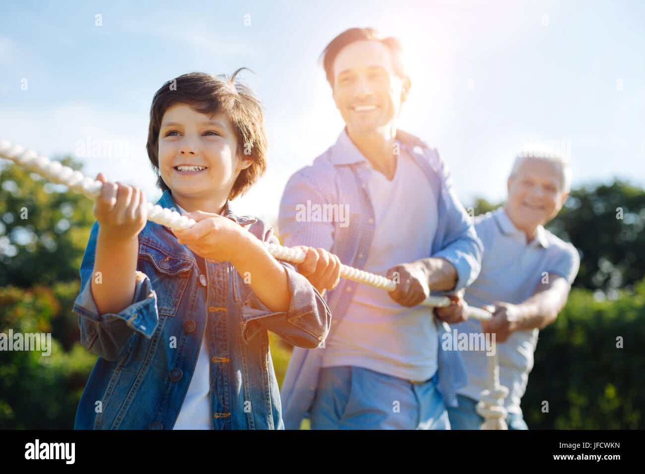 Real support. Enthusiastic focused nice family acting as a team while playing tug war and having fun outdoors in - Stock Image