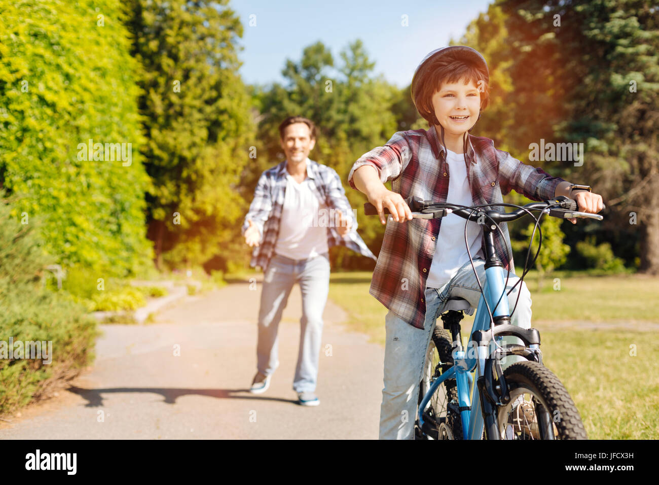 Letting go. Adorable emotional energetic child looking exited while mastering a new skill his father helping him - Stock Image