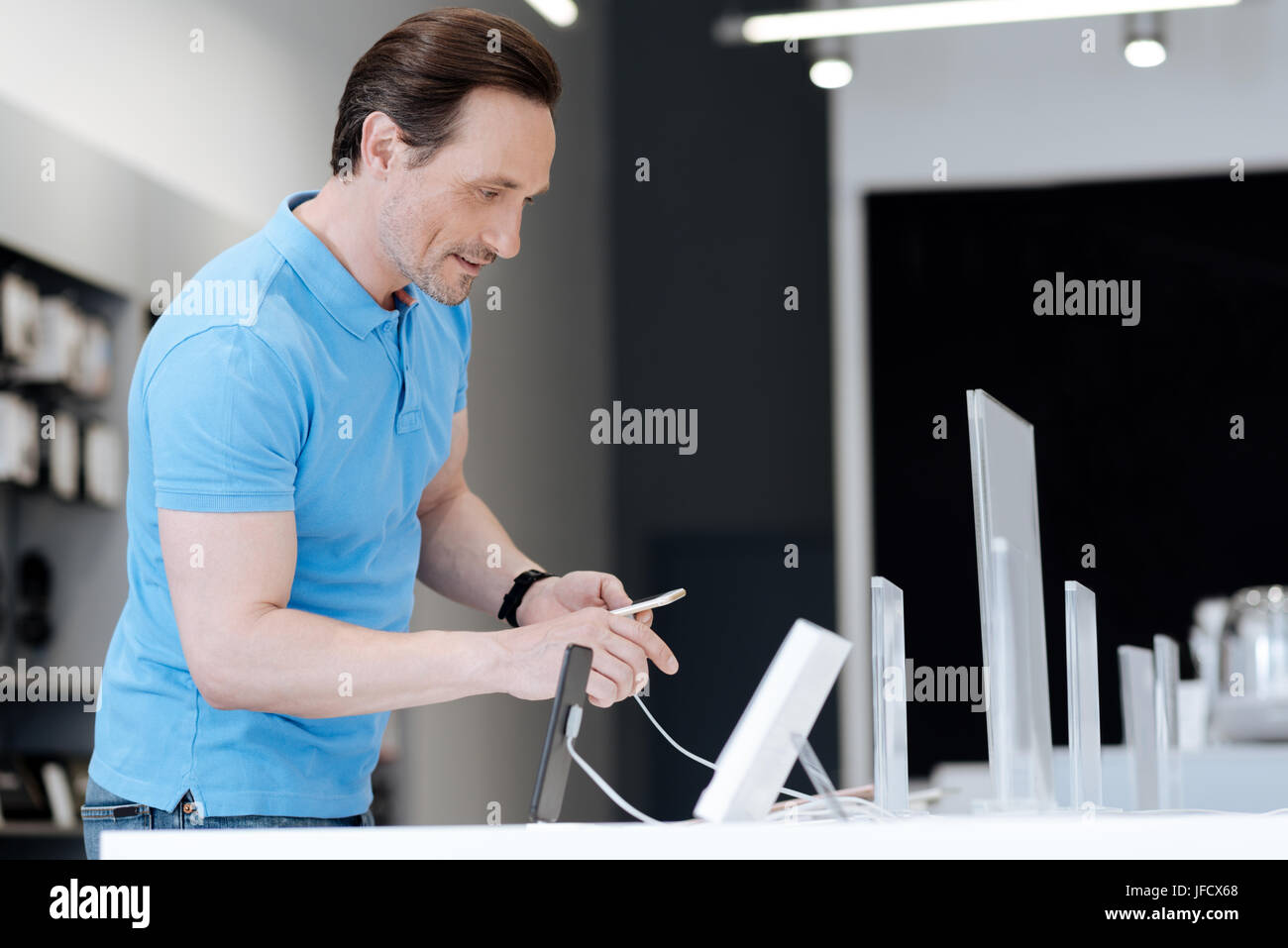 Looking at the main characteristics. Interested adult man wearing a blue polo standing near a store display while - Stock Image