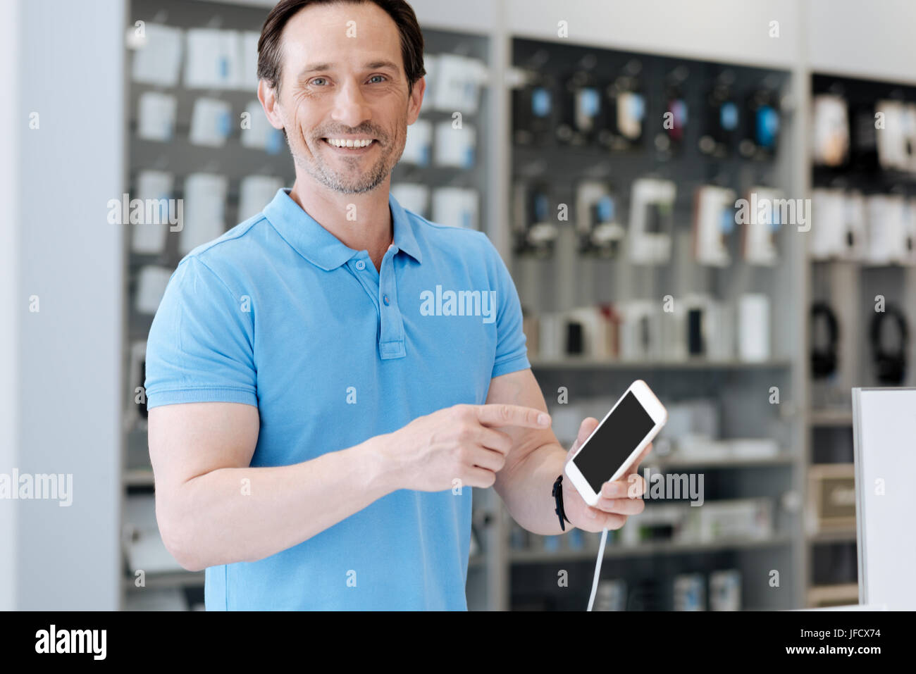 I will take this one. Radiant man grinning broadly while standing at a store display and trying out a cellphone - Stock Image